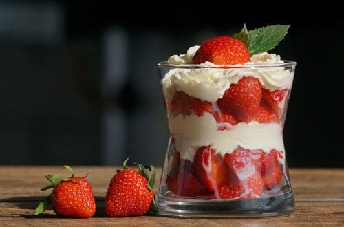 strawberries layered with fruit dip in a small glass