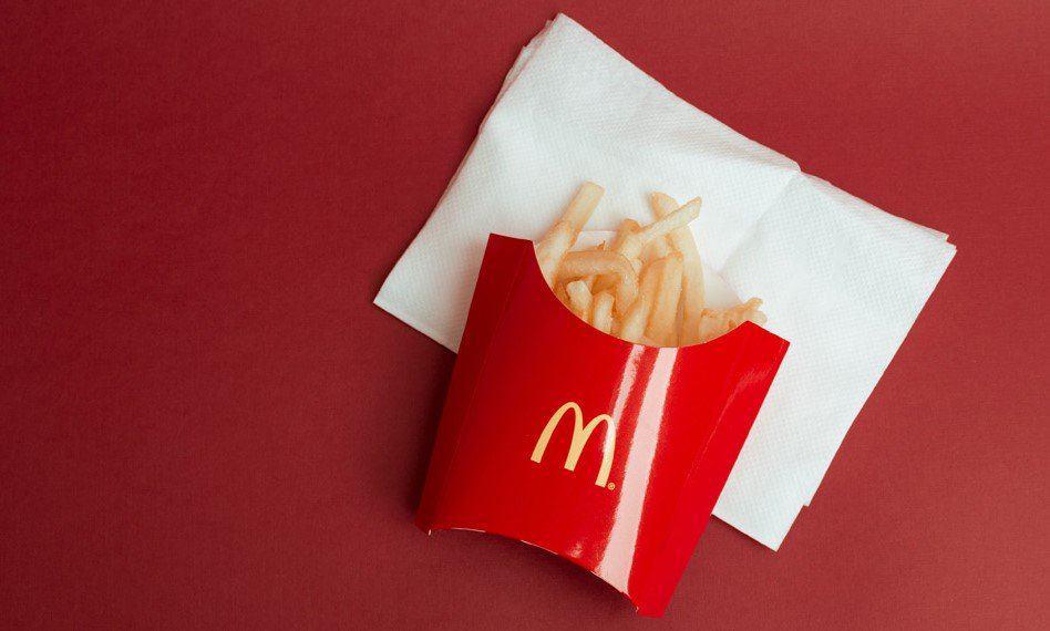 carton of mcdonald's fries on a white napkin