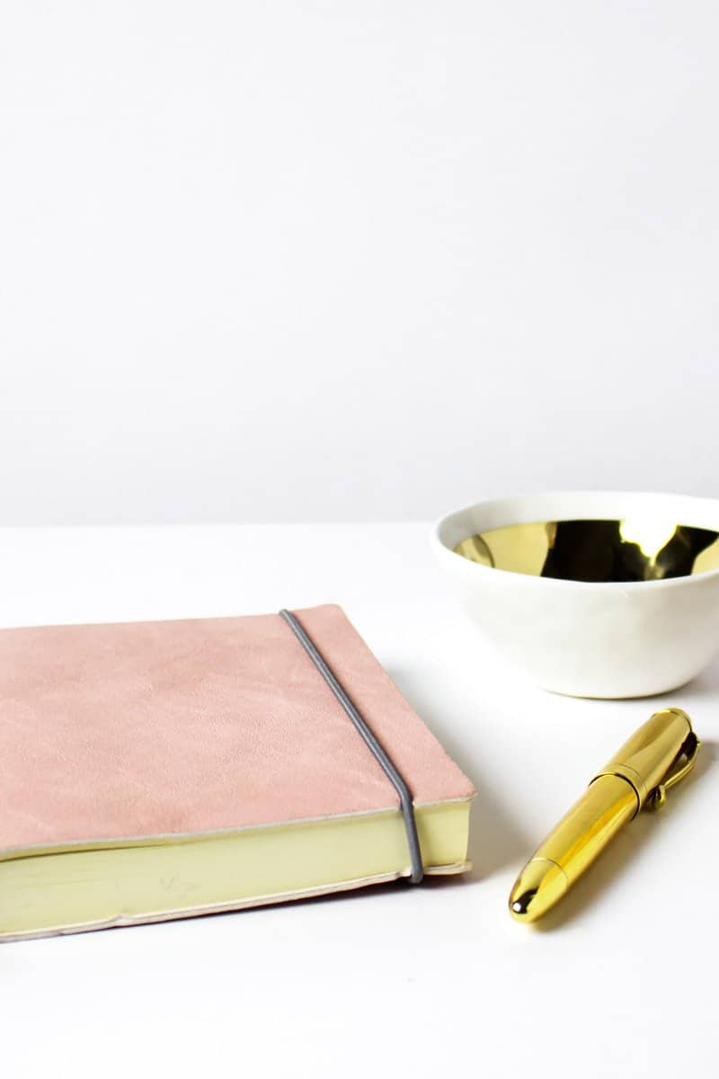 pink bound journal with gold pen