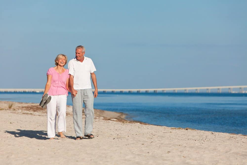 Senior couple walking hand in hand on the sand to help lose weight after 50