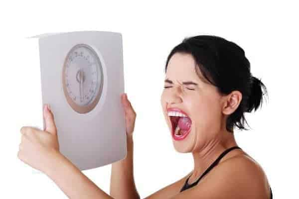 woman holding a scale upset that she gained weight